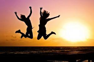 Ľudia skákajúci do výšky od šťastia a radosti