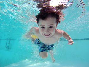 Plávajúci chlapec v bazéne pod vodou